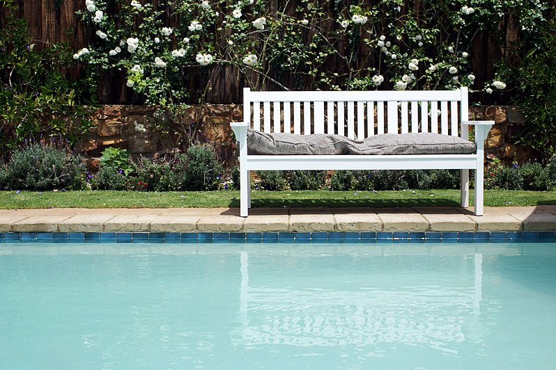landscaped inground pool with bench