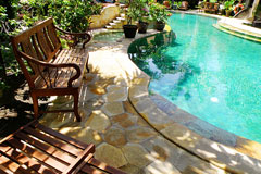 organic shape inground pool with landscaped surroundings