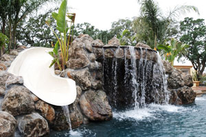 tropical swimming pool with waterfall and waterslide